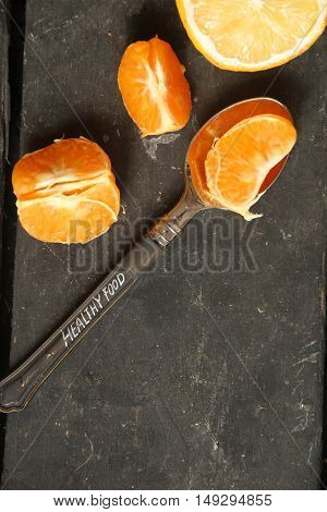 healthy food concept, tangerines and a spoon with text