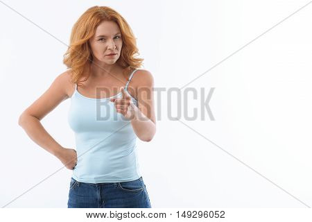 You. Senior woman is pointing finger at camera with seriousness. She is standing with arm akimbo. Isolated and copy space in right side