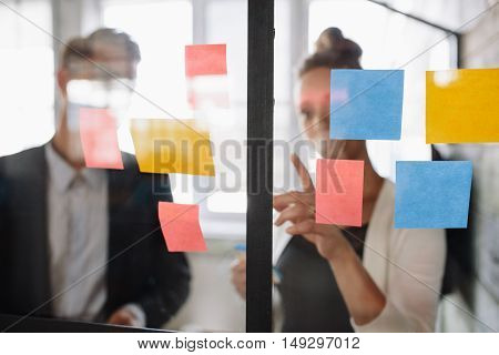 Business Woman Pointing At Sticky Note To Male Colleague