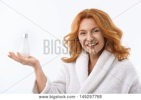 Look at this wonderful lotion. Happy middle-aged woman is holding product and smiling. She is wearing white bathrobe. Isolated