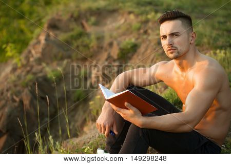 Young handsome man with muscular sexy body and bare chest sitting with book outdoor sunny day