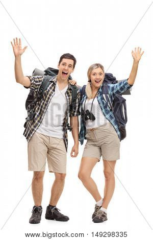 Full length portrait of two happy hikers waving at the camera isolated on white background