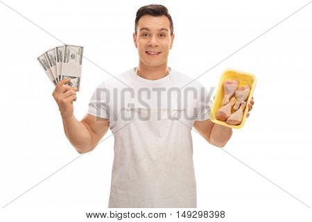 Young butcher holding stacks of money and chicken drums isolated on white background