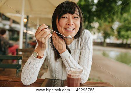 Chinese Female Enjoying Dessert At Cafe