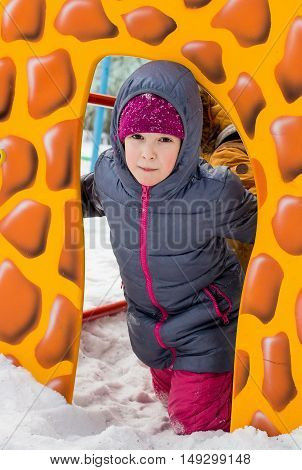Closeup Portrait Of Children In Winter Clothes Outside Playing In The Snow Drifts In The Winter - Ru