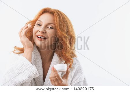 Joyful middle-aged woman is applying cream on her face. She is looking at camera with happiness and smiling. Woman is standing in white bathrobe. Isolated and copy space in right side