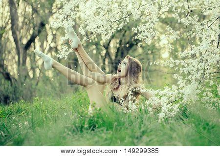 Beautiful happy young woman enjoying beauty in a flowering spring garden