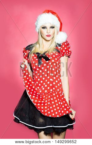 young sexy new year woman or girl with blonde hair and red lips on pretty smiling happy face in christmas santa claus hat and holiday dress in studio on pink background