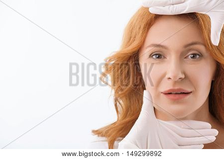 I have perfect facial proportion. Hands in gloves measuring female face as in frame. Excited middle-aged woman is looking at camera with hope and smiling. Isolated and copy space in left side