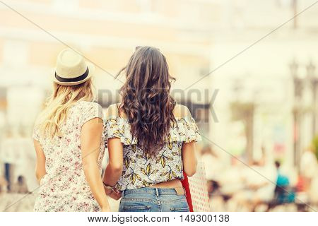 Beautiful girls in shopping. Enjoying sunny day.