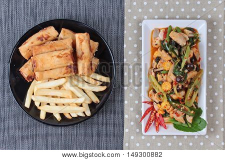 Chinese Vegetable festival  food as fried basil with mixed vegetables served deep fried spring roll and French fries .
