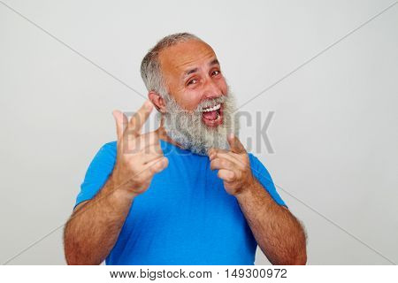 Good-looking elderly man is energetically pointing at the camera with his fingers on white background
