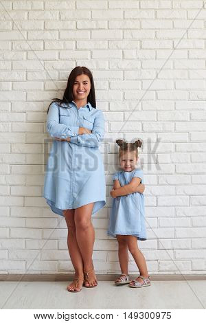 Happy pleased family of mother and her cute daughter smiling with arms crossed against a white brick background