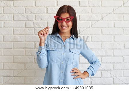 Charming smiling woman in light-blue wear is radiant with the joyful emotions while posing against a white brick background. Female holding a red paper glasses on stick