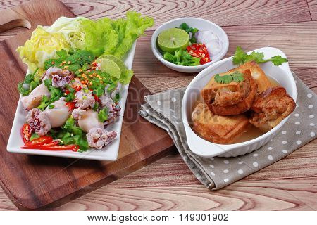Gold bar soup as fried tofu wrap minced pork in soup served with spicy and sour mixed herb salad with squid wrap minced pork on brown