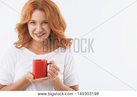 Happy middle-aged woman is standing and drinking tea with enjoyment. She is looking at camera and smiling. Isolated and copy space in right side