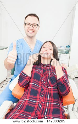 Happy Patient And Doctor In Dentist Chair Showing Thumb Up