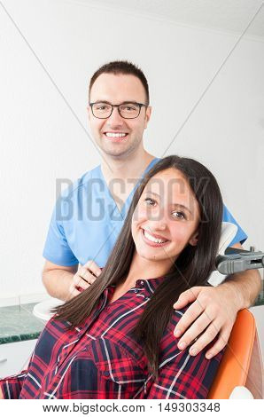 Lady Sitting In Dentist Chair With Doctor Aside