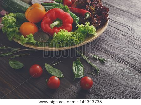 Dish with fresh organic vegetables on wood background. Healthy natural food abundance on rustic wooden table. Cherry tomato, lettuce, pepper and other cooking ingredients