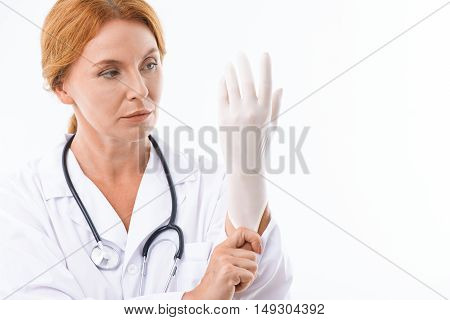 Serious middle-aged doctor is wearing glove with confidence. Woman is standing against isolated background. Copy space in right side