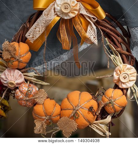 Wreath on the door decorated with handmade textile pumpkins