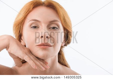 Relaxed senior woman is touching her facial skin gently. She is standing and looking at camera with enjoyment. Isolated and copy space in right side
