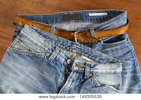 Two pair of blue jeans on a wood surface