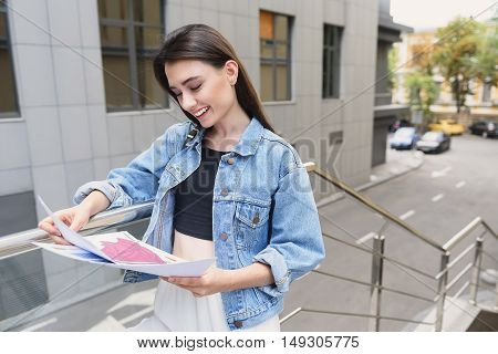 attractive female designer standing on the street with illustrations in her hands