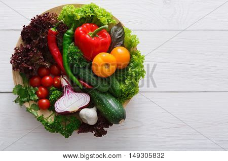 Heap of fresh organic vegetables and greens on white wood background. Healthy natural food abundance on plate with copy space. Tomato, lettuce, carrot and other cooking ingredients top view