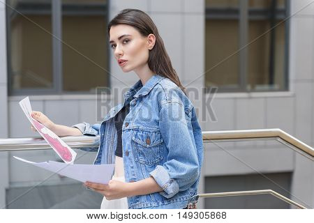student holding her illustrations while standing on the street