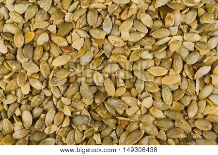 Pile of peeled skinless pumpkin seeds close-up as abstract food background. Lots of healthy vegan and vegetarian food, rich of energy low fat nutrition