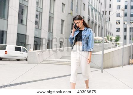 woman walking on the street and talking on her smartphone