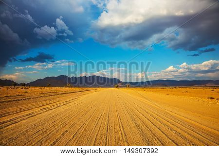 Dirt road in Namib-Naukluft National Park is to the distant mountains. Travel to Namibia. Ecotourism in Africa