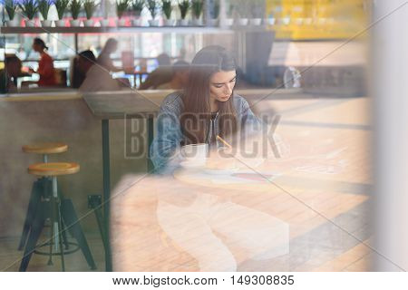 view from the street of a writing woman in the cafe