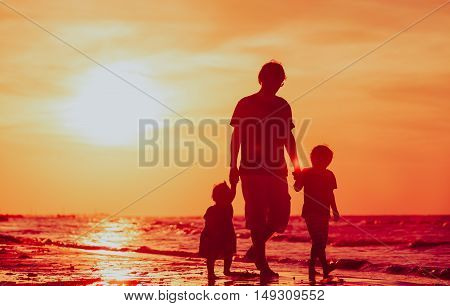 father with little son and daughter walking on beach at sunset