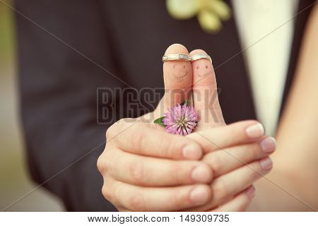 wedding rings on her fingers painted with the bride and groom, funny little men