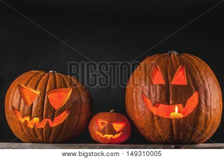 Funny glowing Halloween pumpkins on a black background