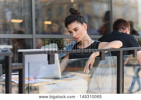 relaxed girl sitting in front of a laptop
