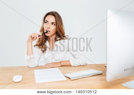 Pensive young businesswoman sitting at the office desk and thinking about something with pen in her mouth