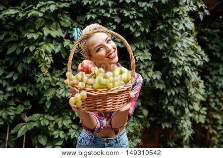 Smiling lovely pin-up girl standing and giving you basket of fresh fruits
