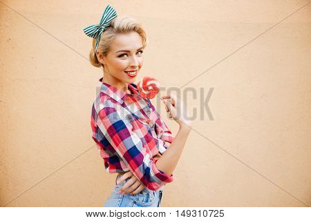 Happy beautiful young woman standing and eating sweet lollipop over pink background