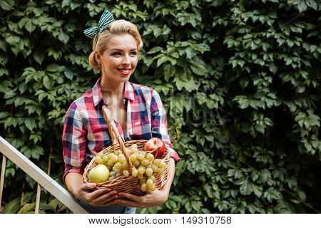 Happy beautiful young woman standing and holding basket with fruits in the garden