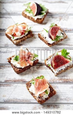 Wholegrain canapes with cream cheese,  ham and figs