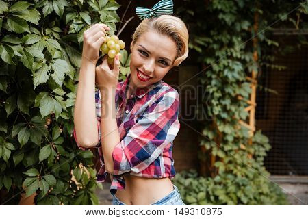 Portrait of cheerful attractive yougn woman with bunch of fresh grape