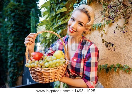 Happy charming pin-up girl with basket of fresh fruits sitting outdoors