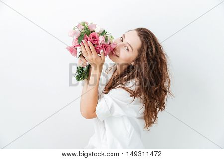 Happy cute young girl smelling flowers over white background