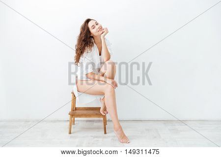 Full length portrait of a charming cheerful woman sitting on the chair isolated on a white background