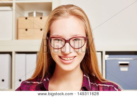 Smiling young blond woman as a student with glasses