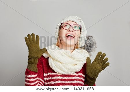 Woman in winter clothing happily looking up