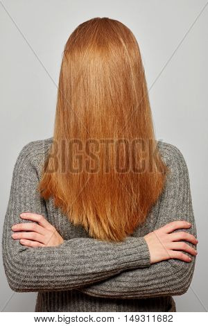 Woman with long and blond hair over her face